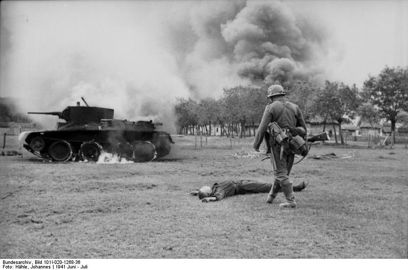 Un soldado alemán contempla un tanquista ruso muerto. También vemos un tanque ligero BT-7 en llamas. Junio 1941
