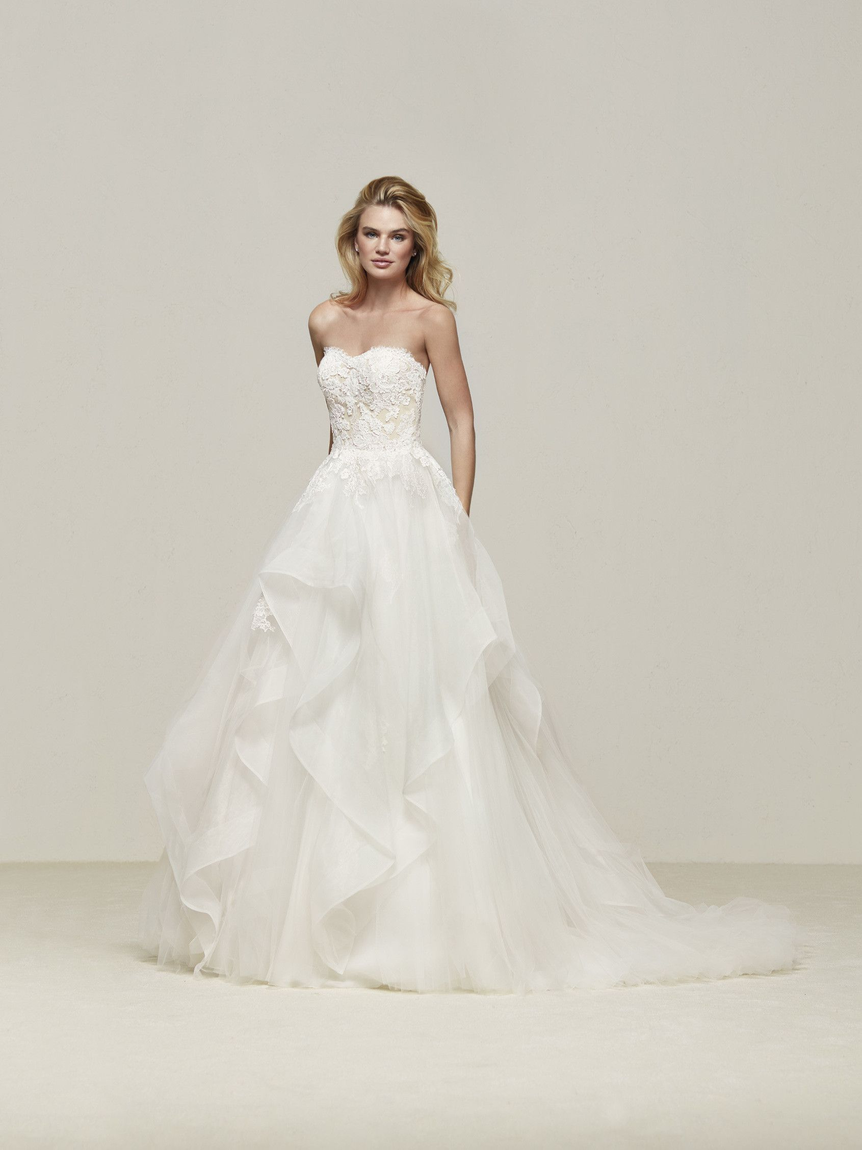 c8dbef333096 Fun and romantic handkerchief skirt ball gown by Pronovias. Available at  Veiled in Elegance.