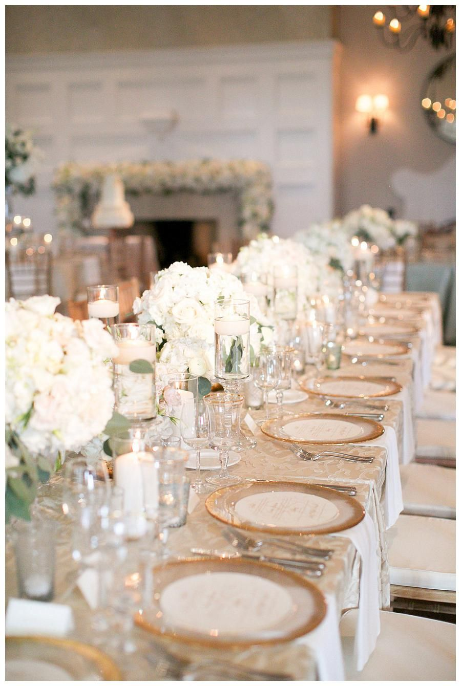 Gold, ivory and white wedding reception tabletop with white centerpiece florals…