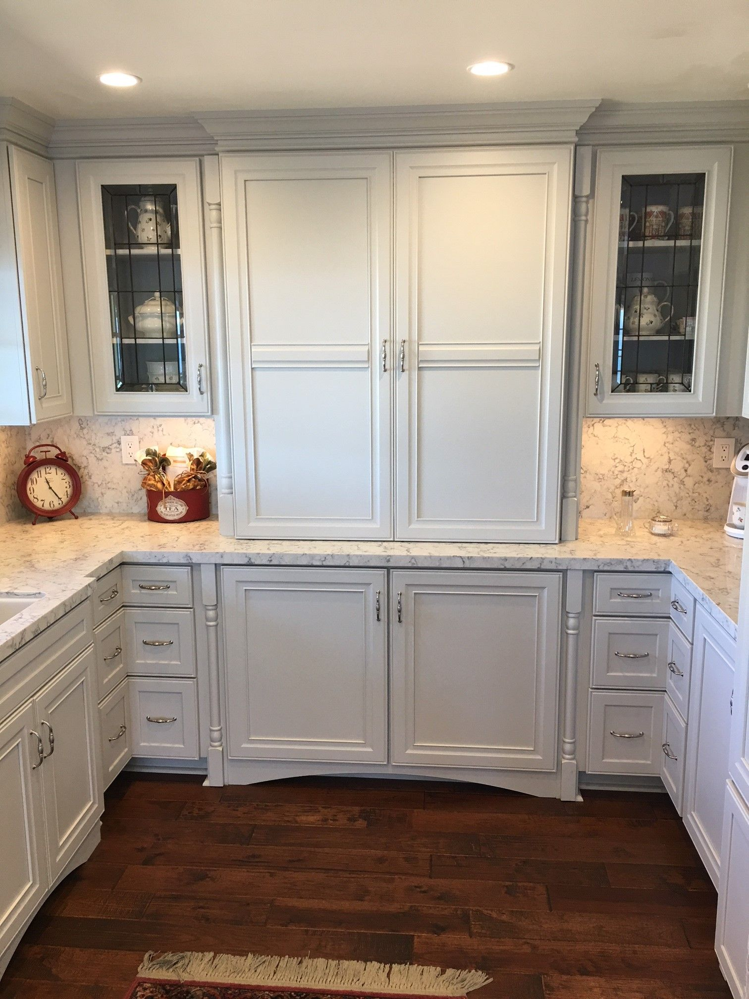 White Cabinets Are Paired With Warm Wood Floors And Granite