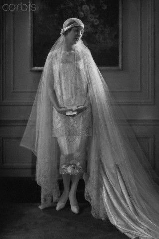 Edna Johnson wearing a 1926 bridal gown designed by Callot Soeurs: silver-brocade satin two-piece dress and train, lace wing sleeves, and a tulle veil held close to the head with a circle of orange blossoms.