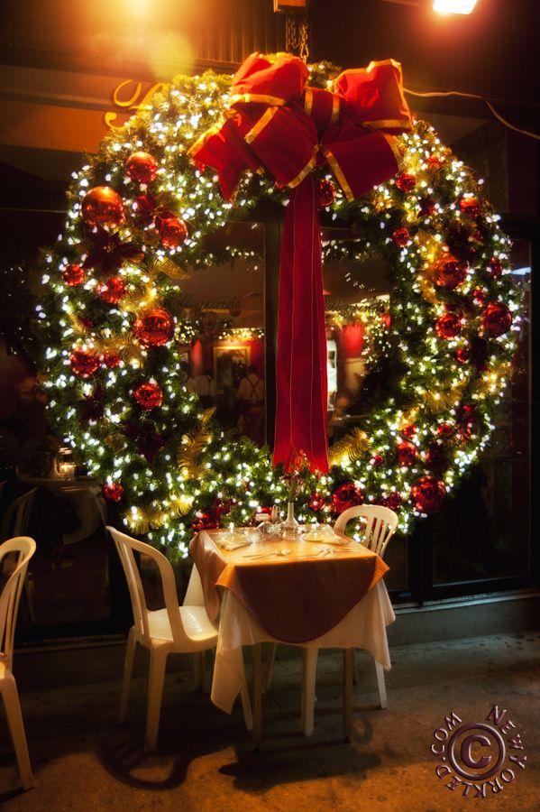A Spectacular Christmas Wreath Adorns A Glass Wall In A Restaurant