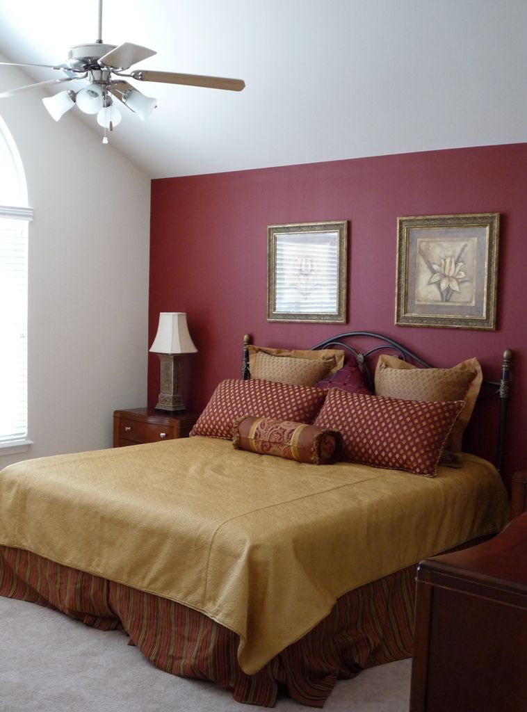 Large master bedroom with red accent wall paint Red