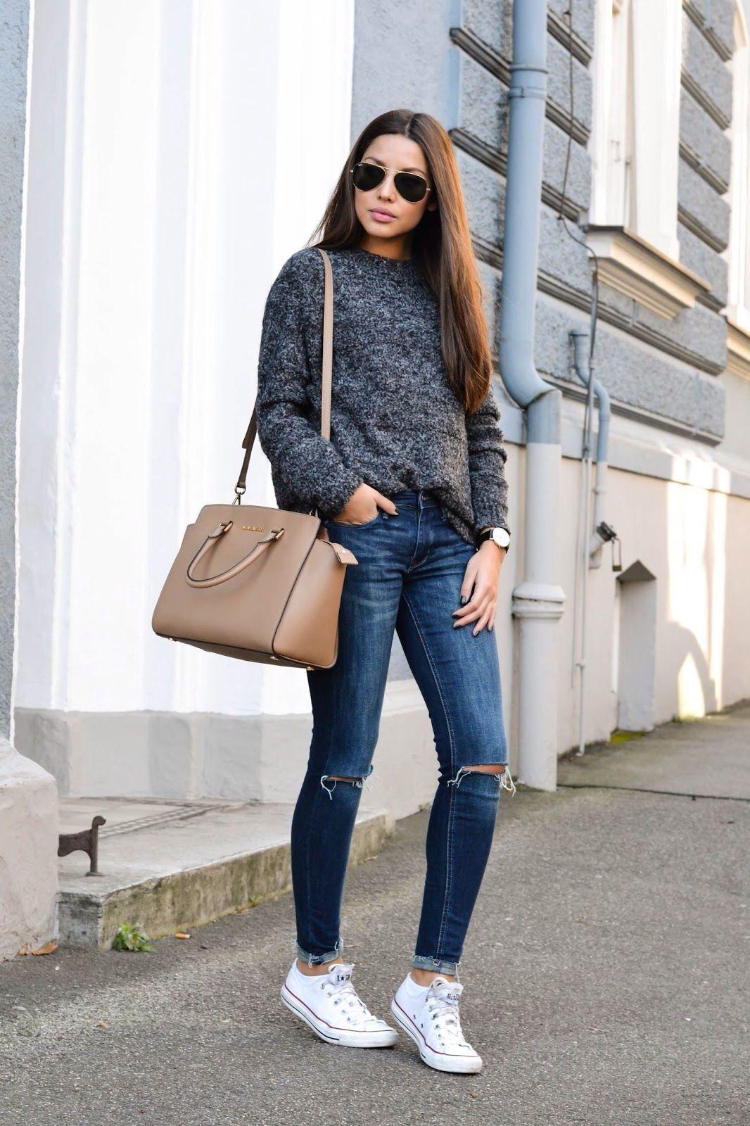 Jeans rotos con suéter de punto gris.