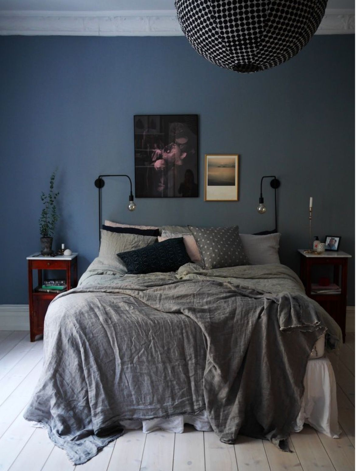 Dark And Moody Bedroom With Navy Blue Painted Walls Gray Bedding A Mix Of Black Throw Pillows Matching Cherry Wood Pedestal Nightstands