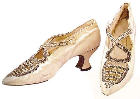 A pair of white satin strapped shoes from the first decade of the twentieth century, intricately beaded and fastened with pearls.