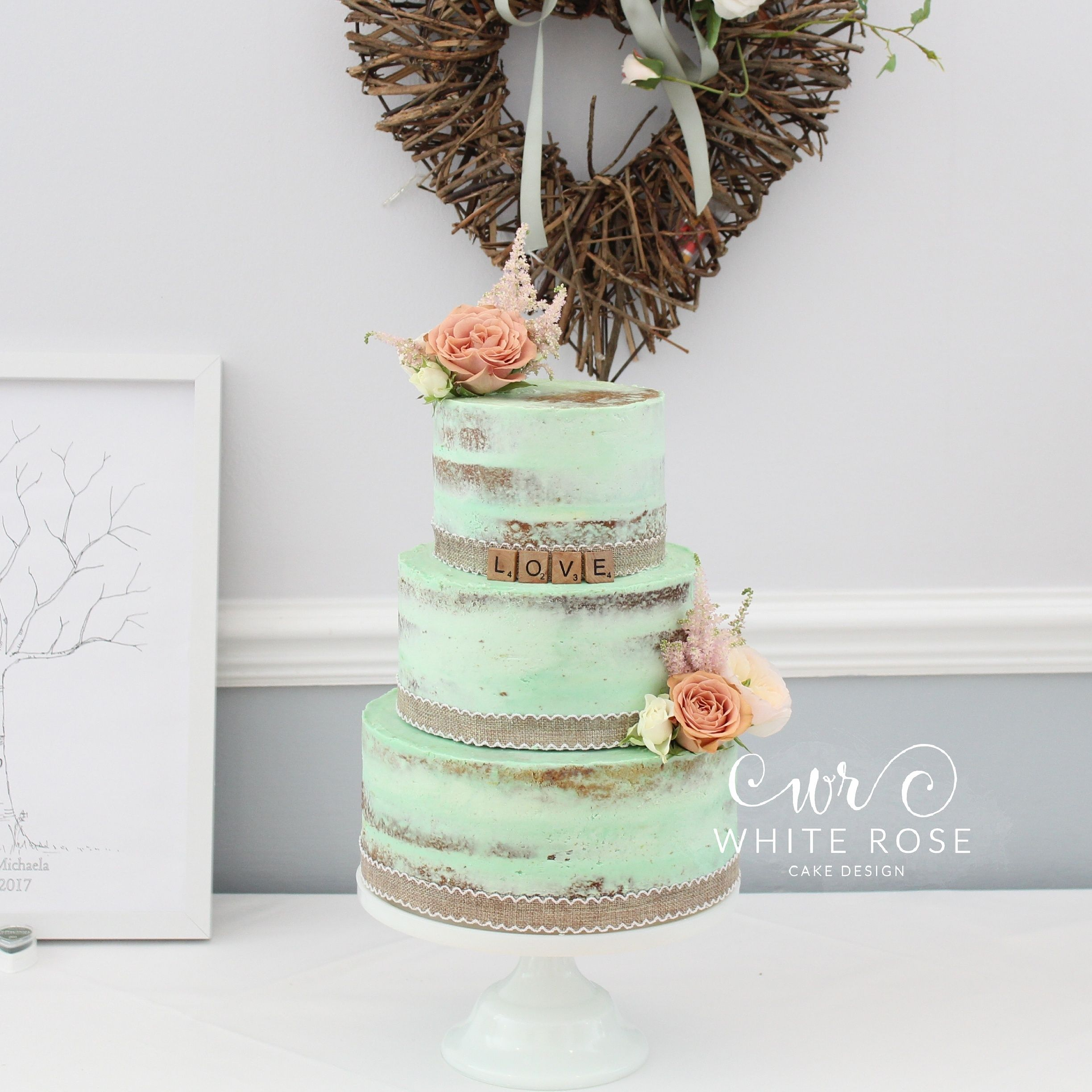 A rustic mint and peach wedding cake dressed with fresh flowers at ...