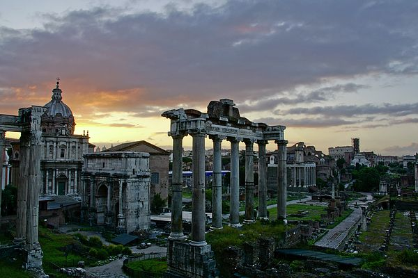 The beautifully lit sky at sunrise over the Roman Forum with the church of Santi Luca e Martina in the background.