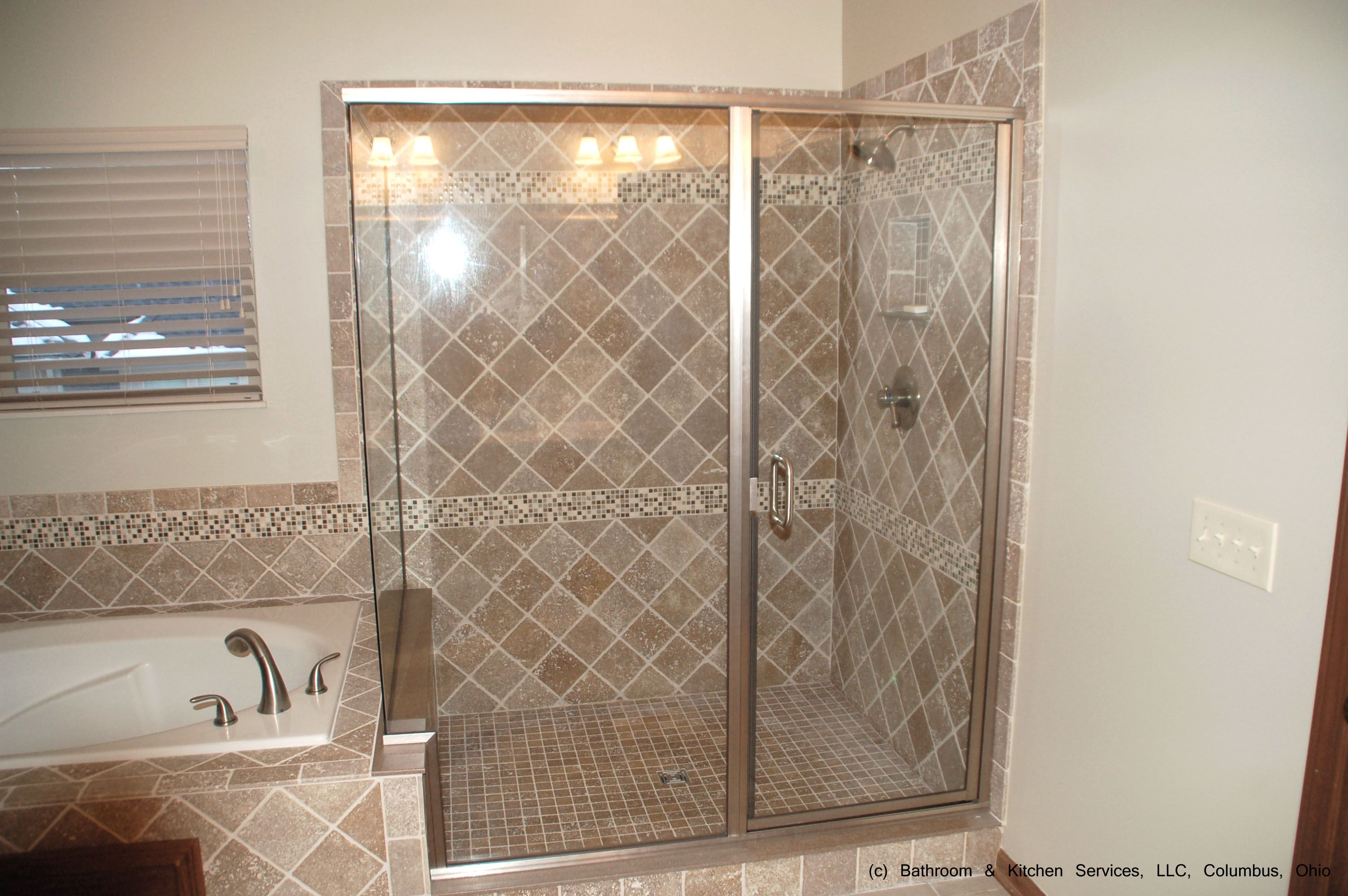 Shower and tub tile carry design continuity in this custom layout.  Square tile on shower floor balances diagonal tile and smaller square tile bands for cohesive and interesting look.