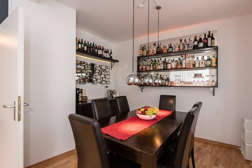 Modern Eingerichteter Essbereich Mit Silberfarbener Pendelleuchte Und  Weinregalen. #Esszimmer #Einrichtung #Pendelleuchte #