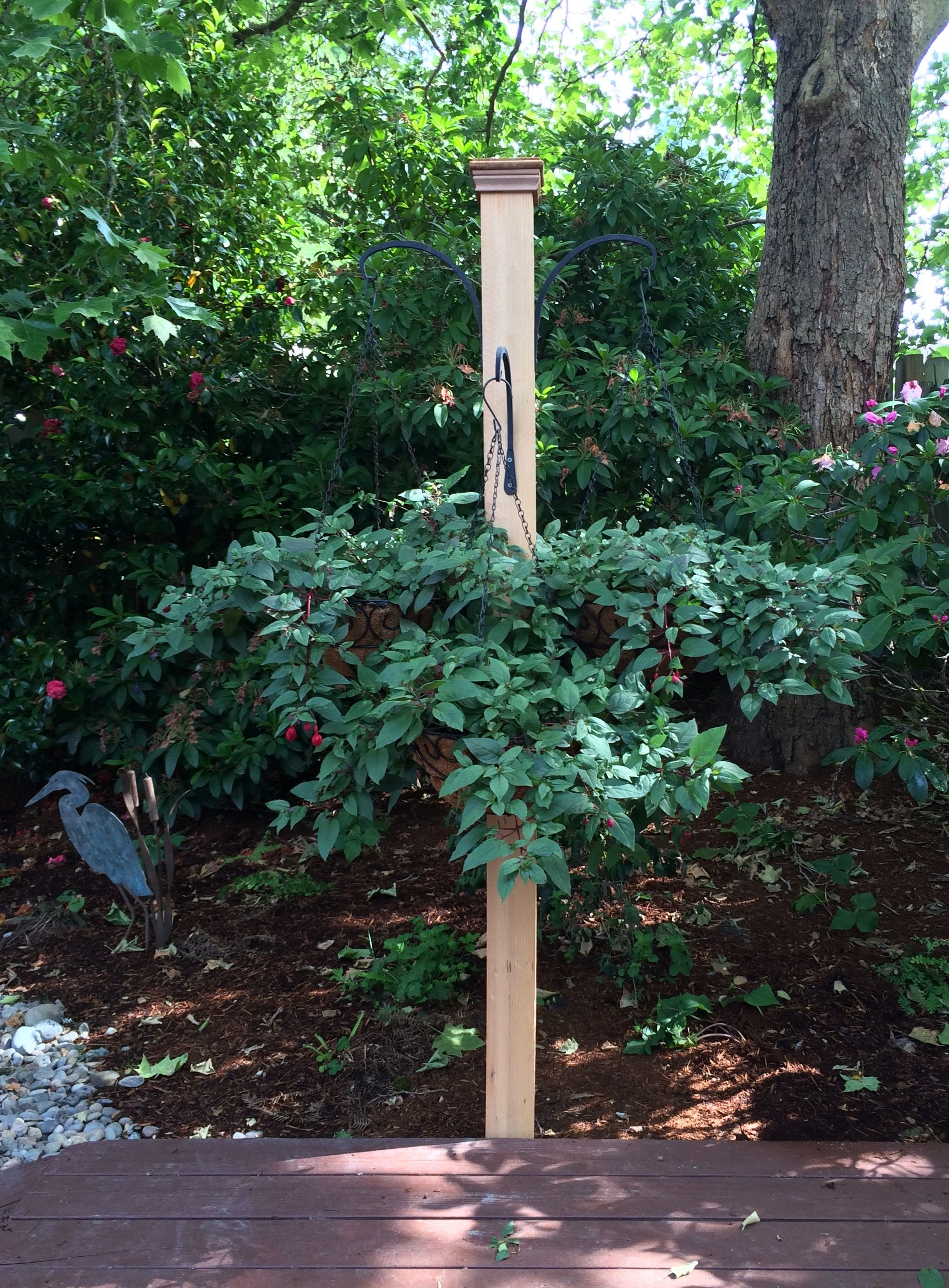 Fence post basket hanger. One eight foot 4x4 post with four black ...