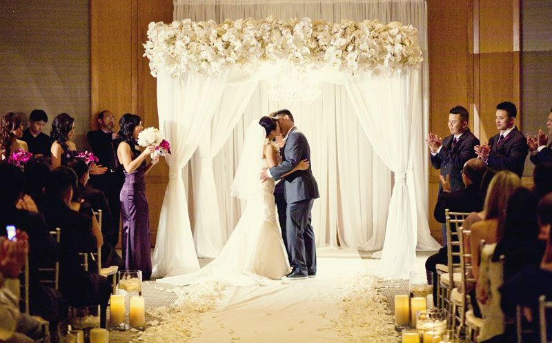 fabric chuppah with white floral accent and crystal chandelier