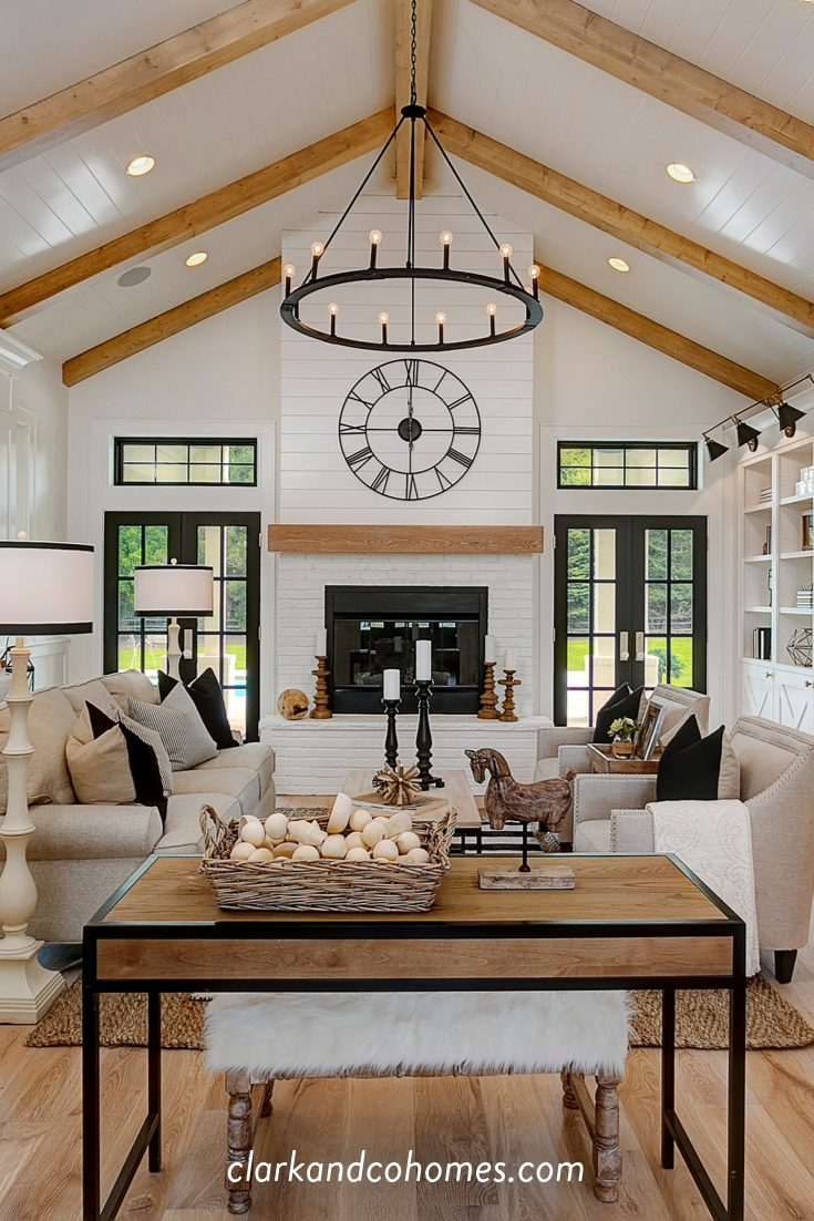 The great room in this Modern Farmhouse home features a custom painted brick and shiplap fireplace with a wood stained mantle that coordinates with the natural wood beams of the vaulted ceiling. #modernfarmhouse #vaultedceiling #beams #fireplace #shiplap #paintedbrick #blackandwhite