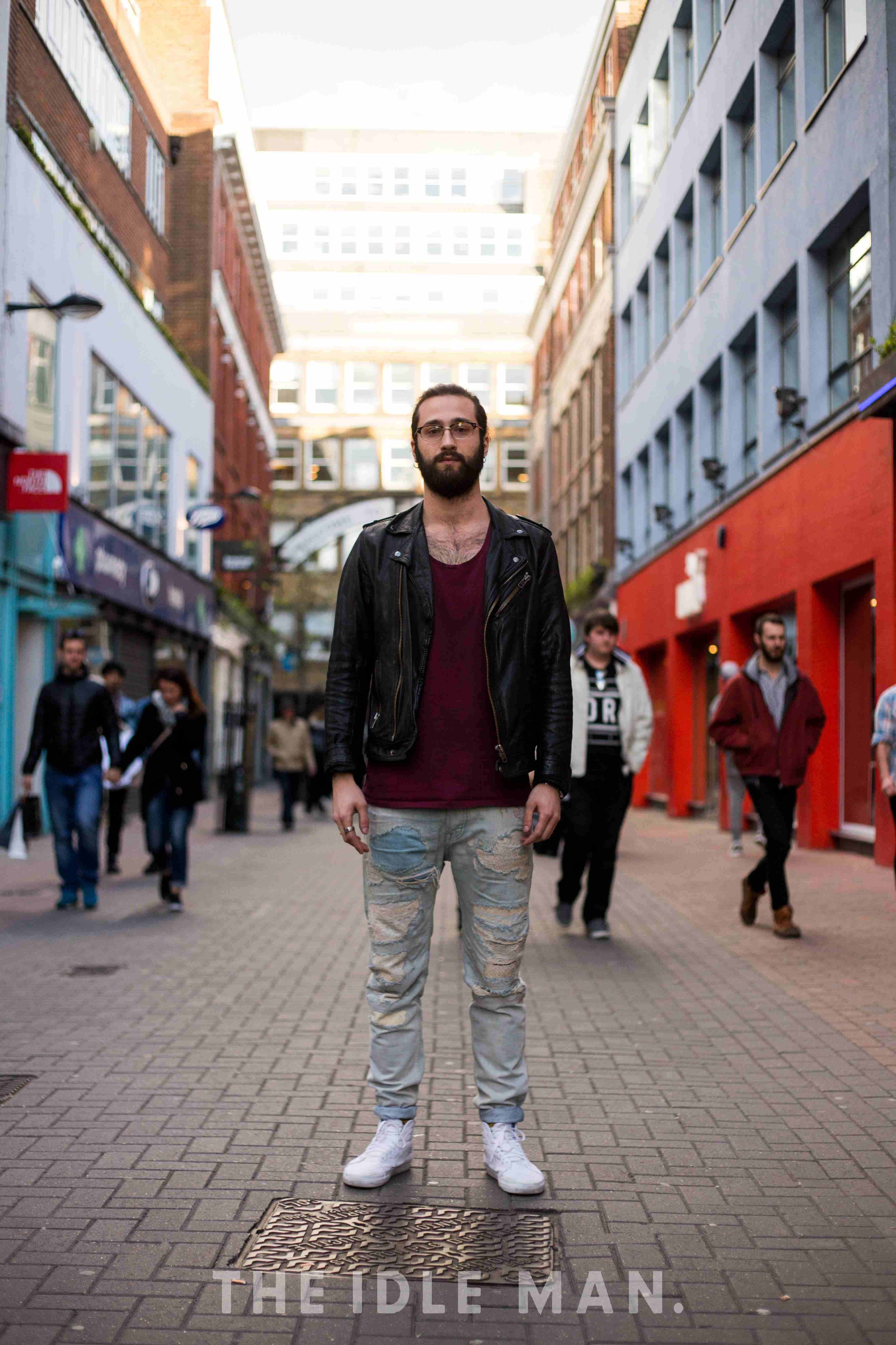 Urban Distressing | Layer a red or maroon vest or t-shirt underneath a leather biker jacket, add a pair of light wash distressed jeans and finish the outfit with a pair of white hi tops. | Shop men's clothing at The Idle Man
