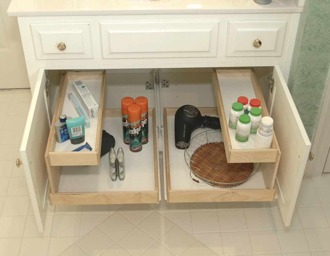 white wooden bathroom cabinet with pull out sliding shelves and top drawers to put toiletries on
