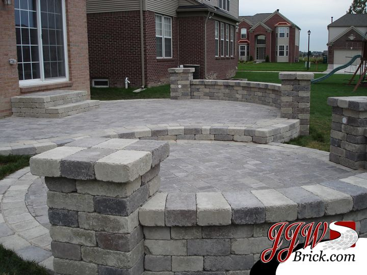 two tier brick paver patio design with brick pillars and seating