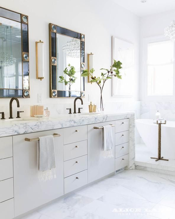 Two Gold And Black Vanity Mirrors Are Mounted To A White Wall And Flanked  By Calliope