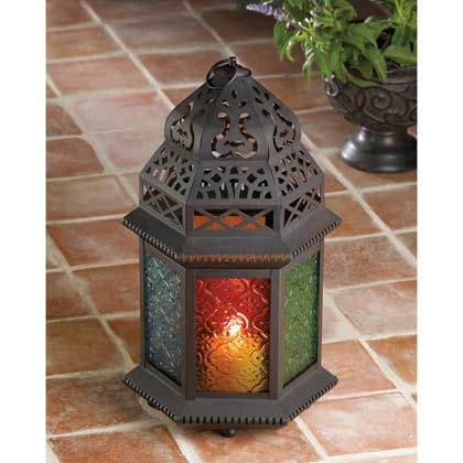 """The graceful cutouts in this candle lantern's shell throw dancing laceworks of light, while patterned multi-colored glass panels cast a halo of color. Suitable for hanging, or use as a free-standing lamp.    Uses pillar or votive candles (not included). Metal with colored glass panels. 6 1/2"""" x 7..."""
