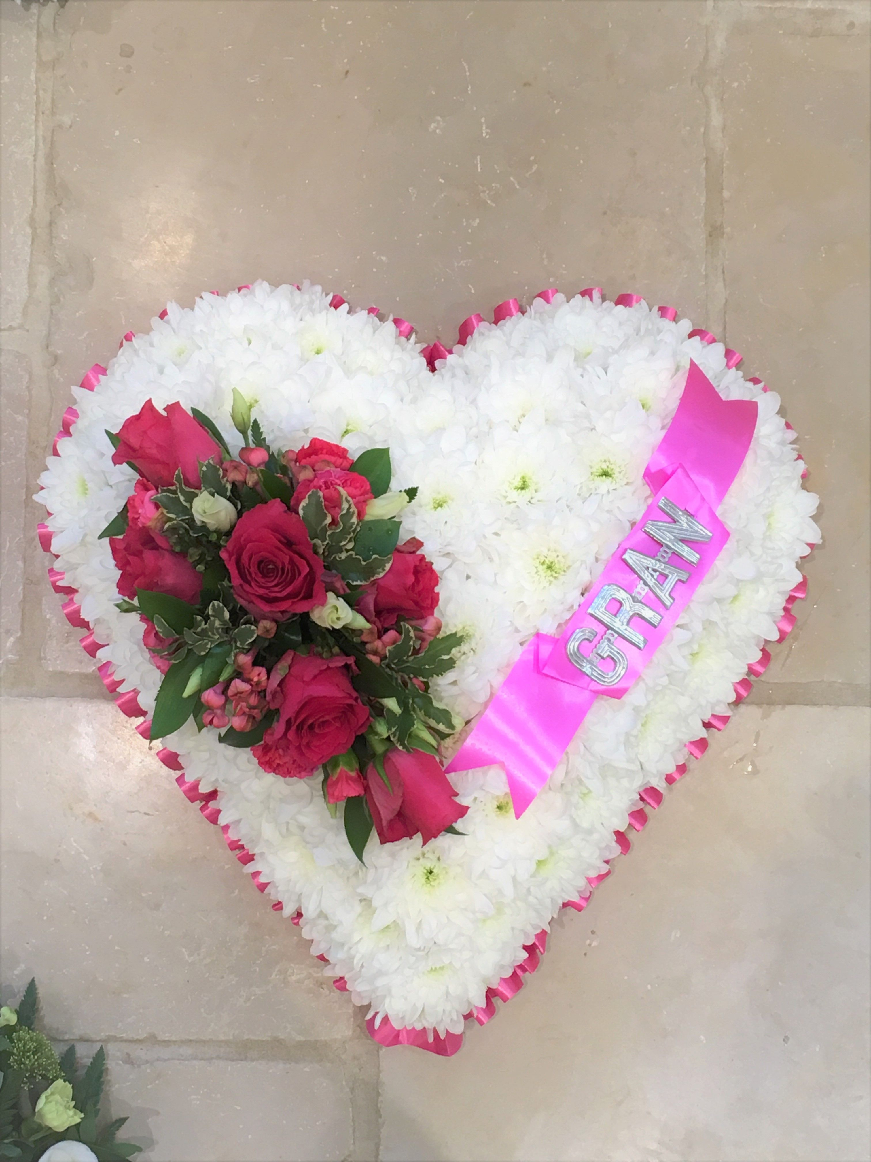 Pretty cerise pink rose spray on white chrysanthemum based heart pretty cerise pink rose spray on white chrysanthemum based heart funeral tribute with gran banner izmirmasajfo