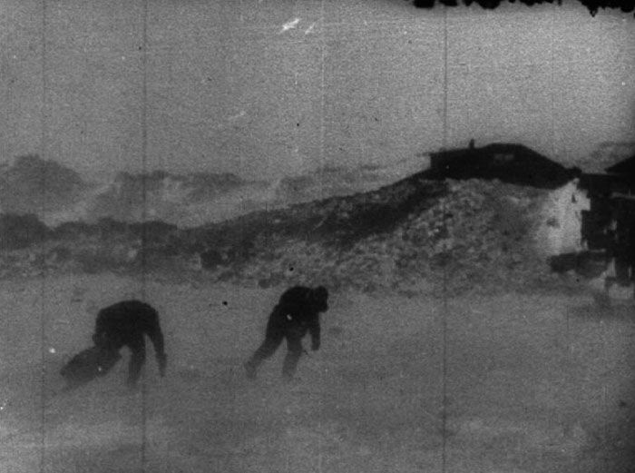 Two men struggling to walk through the snow and against heavy wind.