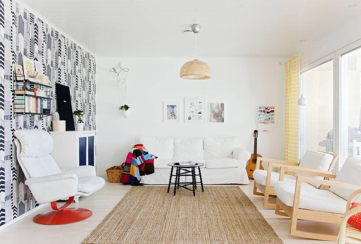 Olohuoneessa on talon ainoa tapetoitu seinä. Rilla valitsi siihen ajattoman Marimekon Ruutukaava-tapetin. Juuttimatto ja sohva on hankittu Ikeasta, keinutuolit kirpputorilta ja vanha kaappi on itse maalattu.