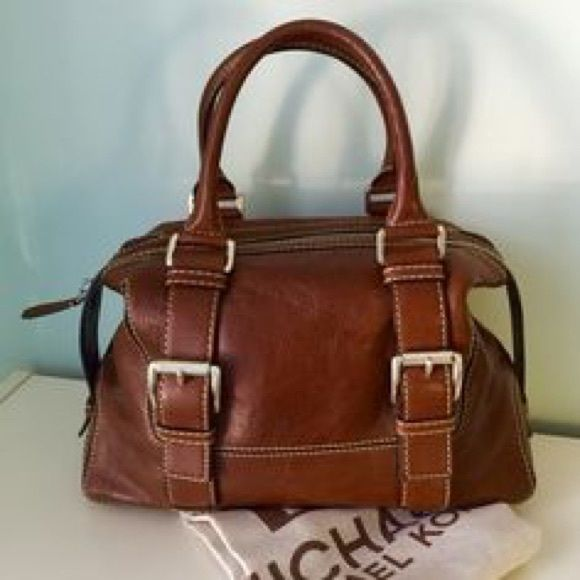 Brown leather bowler bag White stitching. Two silver buckles on front.  Zipper compartment and two pockets inside. In perfect condition. MICHAEL Michael Kors Bags