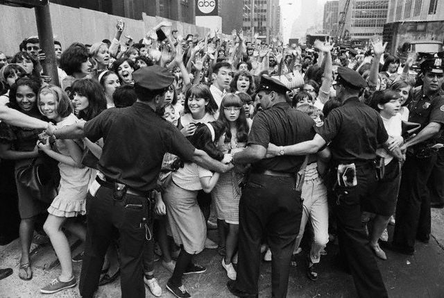 13 Aug 1965, Manhattan, New York, New York, USA --- 8/13/1965-New York, NY- New York City policemen try to restrain hordes of teenagers- mostly of the female variety -from crashing into the Warwick Hotel, the Beatles' New York residence, August 12. The Beatles appear at Shea Stadium August 15, their only New York concert on their current U.S. tour.