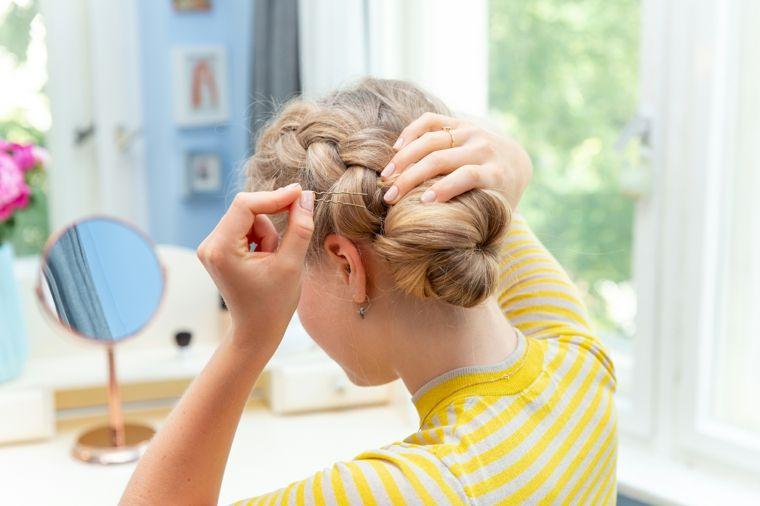 Pettinatura facile con uno chignon e una treccia laterale per dei capelli  lunghi e biondi 49b4430ca53d