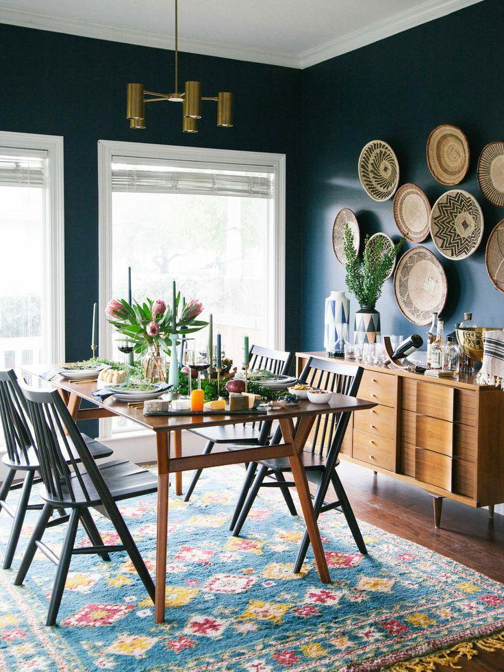 earthy and modern dining room   dark navy walls   brass light