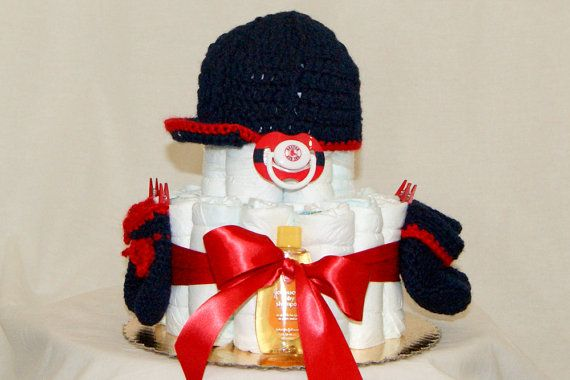 $65 I just added this Red Sox Themed Diaper Cake to my store on Etsy,   Check out this and other themes at keepsakediapercakes1.etsy.com Ingredients include: 27 Premium quality Pampers (size 1), Hand Crocheted baseball cap and booties, bottle and matching binkie. Johnson and Johnson's baby soap, shampoo, lotion and Desitin creme. Embellished with baby cloths pins and matching ribbon. Our cakes do not fall apart, we guarantee satisfaction!