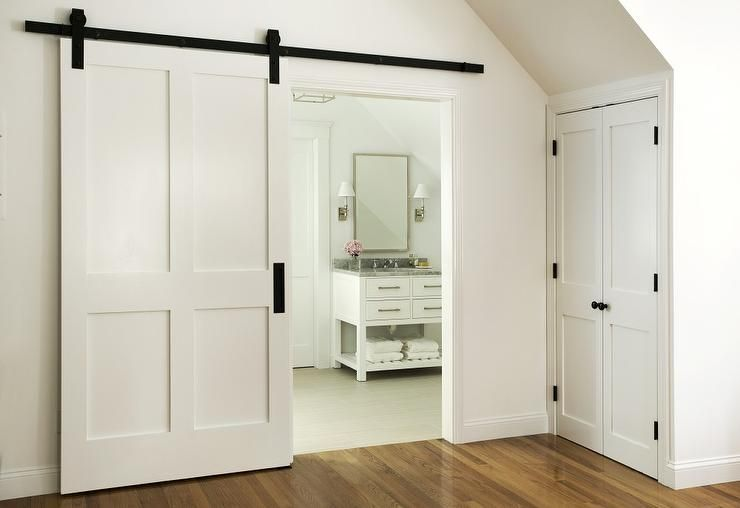 A White Barn Door On Rails Opens To An En Suite Bathroom