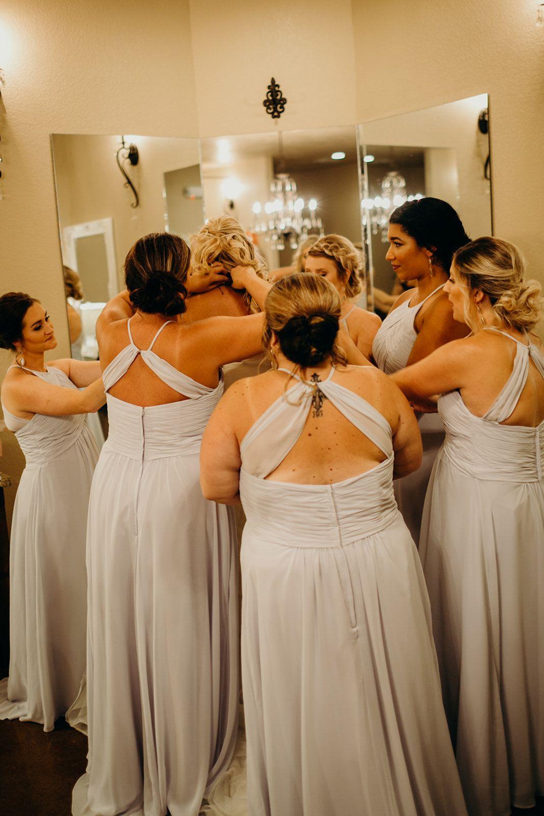 Wedding dresses tulsa  candid bridesmaid photo  bridesmaids helping the bride get her