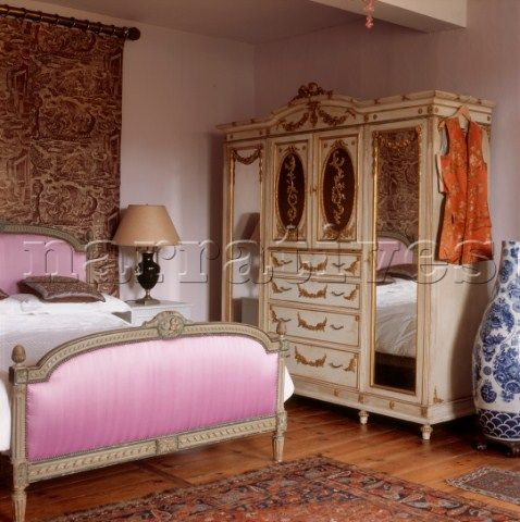 Ornate French Period Style Bedroom With Pink Velvet Fabric Covered Bedstead And Decorative Gold Leaf