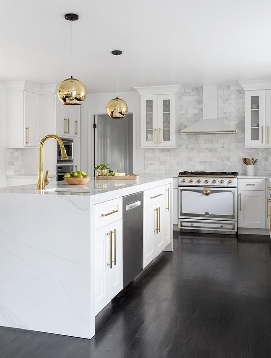 stunning kitchen featuring a white quartz waterfall island with white shaker cabinets brass on kitchen island ideas white quartz id=38558