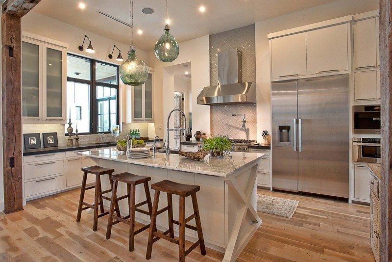 Cocina abierta, grande y repleta de todos los utensilios necesarios. Toques de color en puntos claves y combinándolo con el mármol y la madera clara.