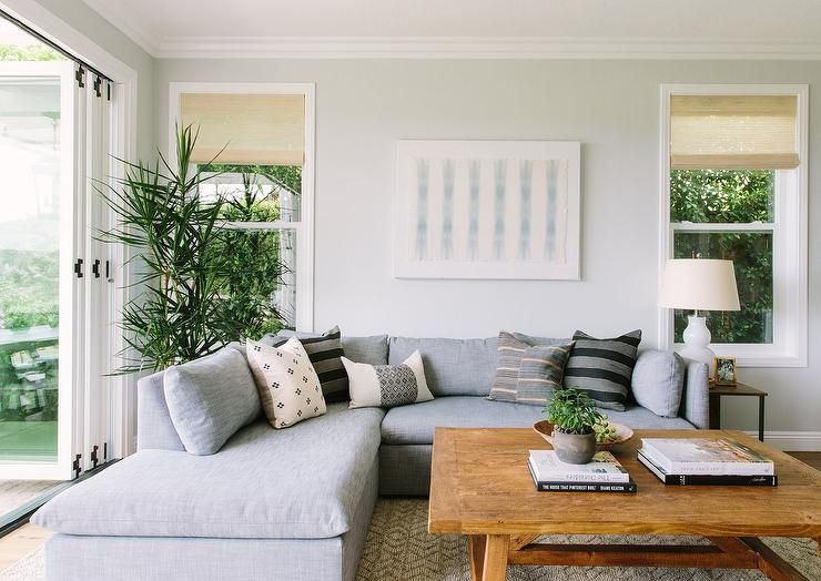 A Low Gray Sectional Fitted With A Chaise Lounge Is Placed On A Cream Rug Beneath A Cream And B Transitional Living Rooms Transitional House Transitional Decor