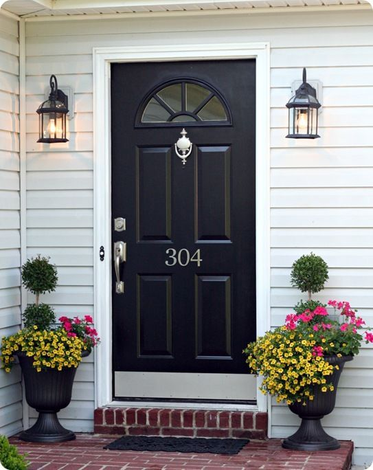 Black Painted Front Door; Black Lantern Porch Lights; Large Urns With  Geraniums, Million