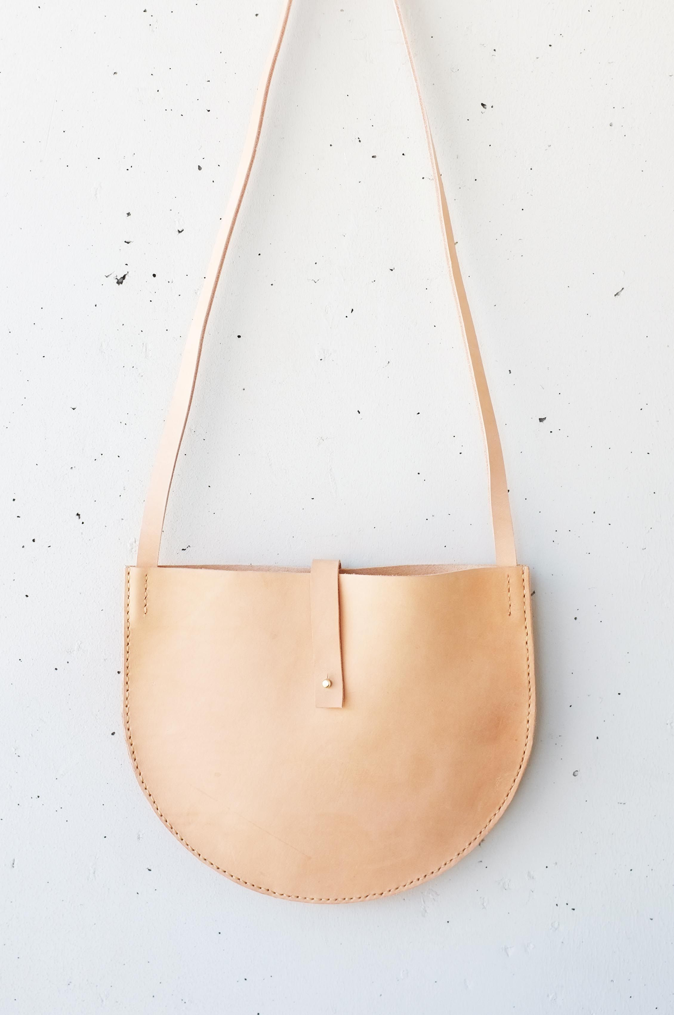 Round Cross Over Bag - Made out of vegetable tanned leather and has a natural color that will go darker and more beautiful with time.The bag has a strap lock to secure your carrying.   Measurements: 30cm x 24.5cm  Handcrafted by Emma Wright