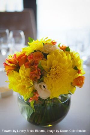 Bright yellow and orange posey in fishbowl vase for table centrepiece