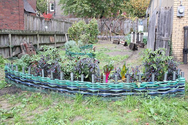 a wattle fence made of salvaged steel pipe and old garden hoses ...