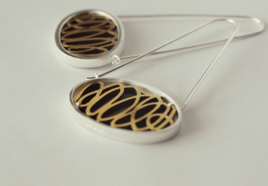 Oval pieces with a silver frame around a form of brass squiggles. #Earrings #Maisa #Joidart