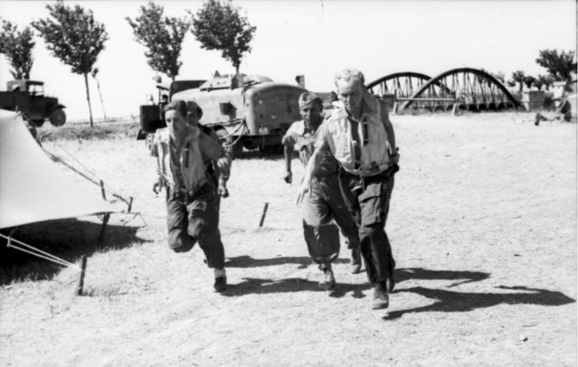 """1943 Italien-Süd.- Piloten (des Jagdgeschwader 51 """"Mölders"""" (JG 51) ?) mit angelegten Schwimmwesten auf einem Feldflugplatz, laufend (Alarmstart ?)"""