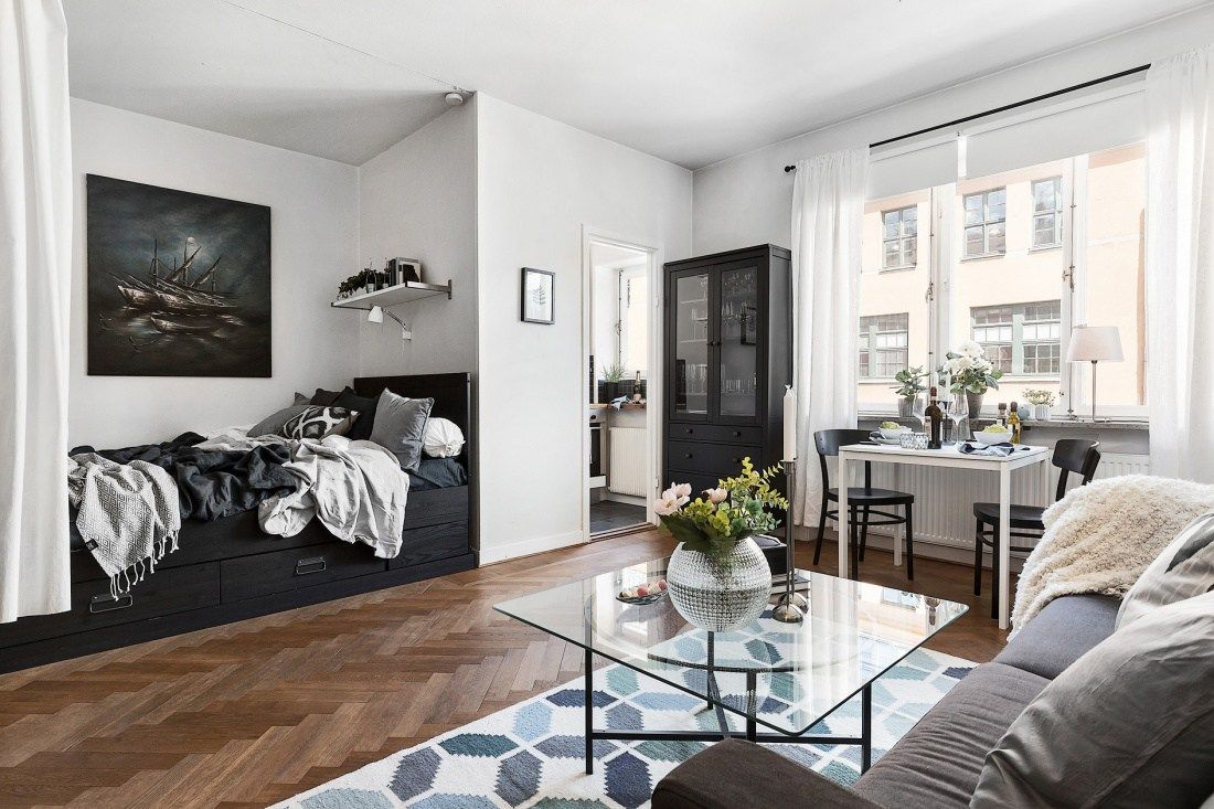 black and white studio apartment with a nook for the platform bed placed on top of drawers with