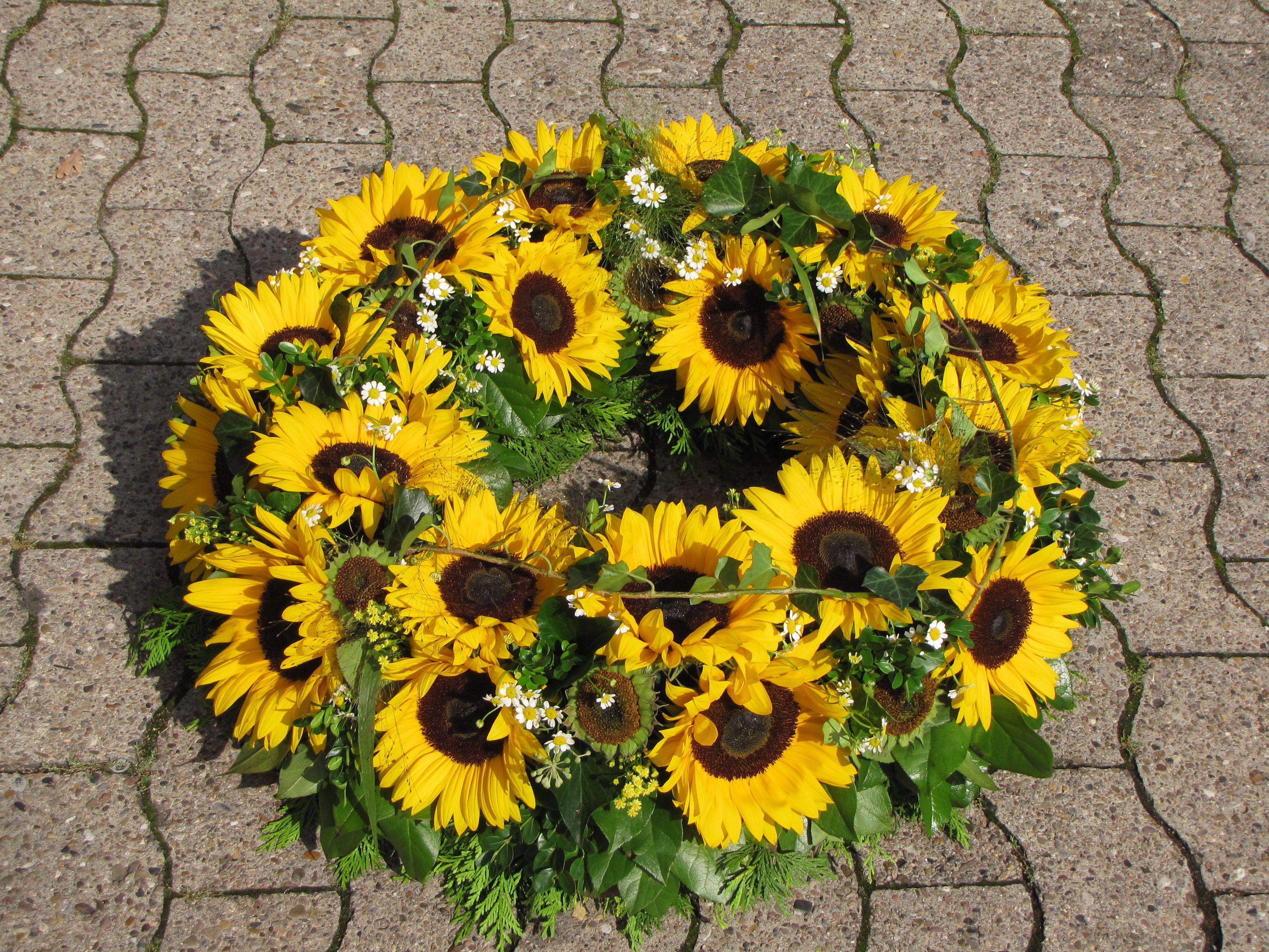 rundgesteckter trauerkranz mit sonnenblumen sie symbolisieren das strahlen eines. Black Bedroom Furniture Sets. Home Design Ideas