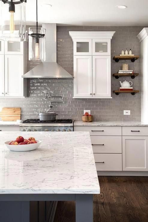 Transitional white and gray kitchen is fitted with many features including small stacked industrial wood and iron shelves. The stacked shelves are flanked by white shaker cabinets mounted on glossy gray subway tile backsplash over white and gray quartz countertops.  Kitchen inspiration by @windmillhill  #kitchenchronicles #kitchendiaries #kitchendesign #dreamkitchen #kitcheninspiration #kitchenstyle #kitchengoals #kitchenideas #kitchendesignideas #kitcheni #graykitchen #whiteshakercabinets