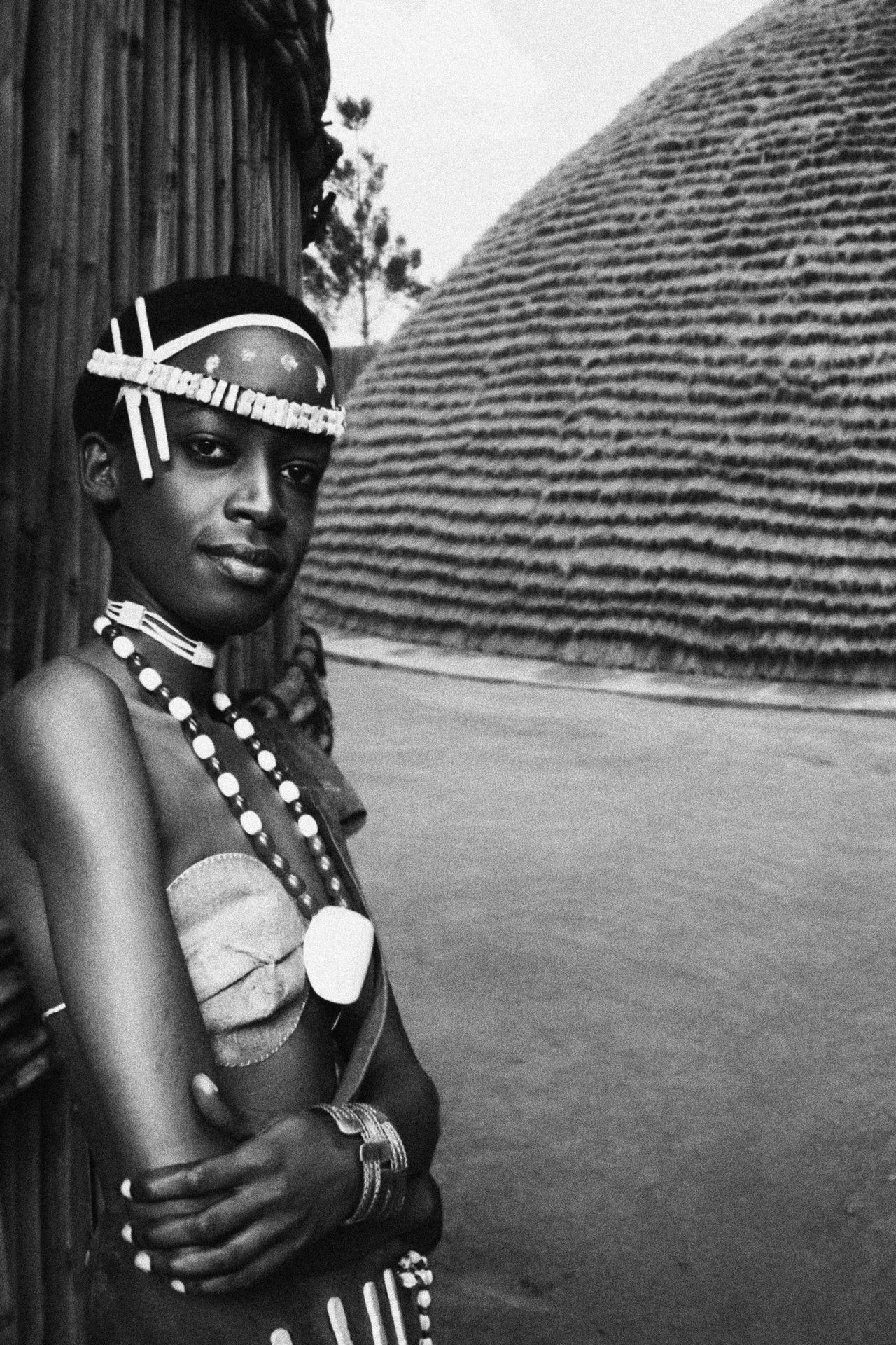 Girl in traditional attire. Grass hut in background, probably on royal grounds. Rwanda