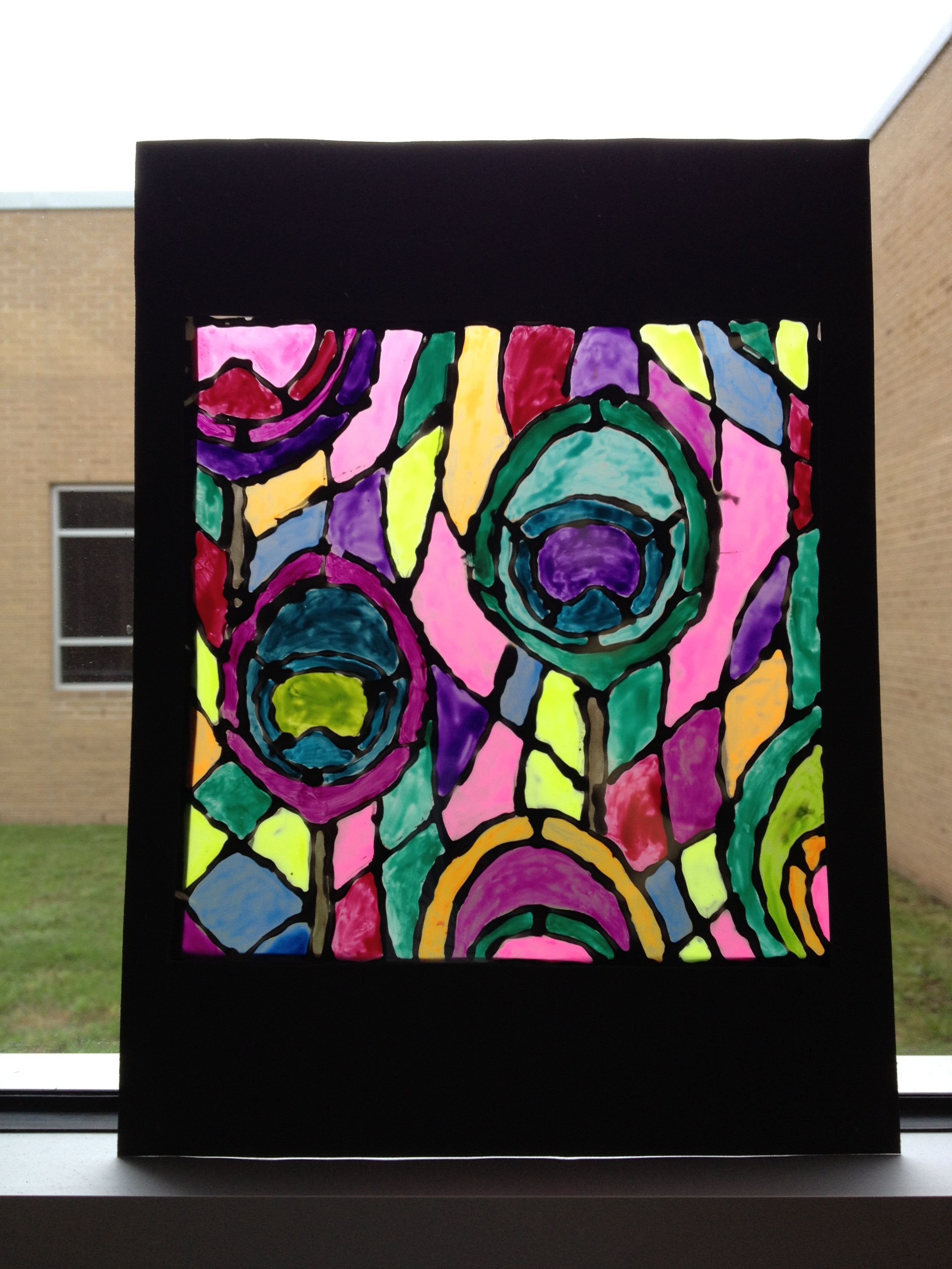 """5th Grade """"stained glass"""" art created using a  transparency, black glue and paint."""