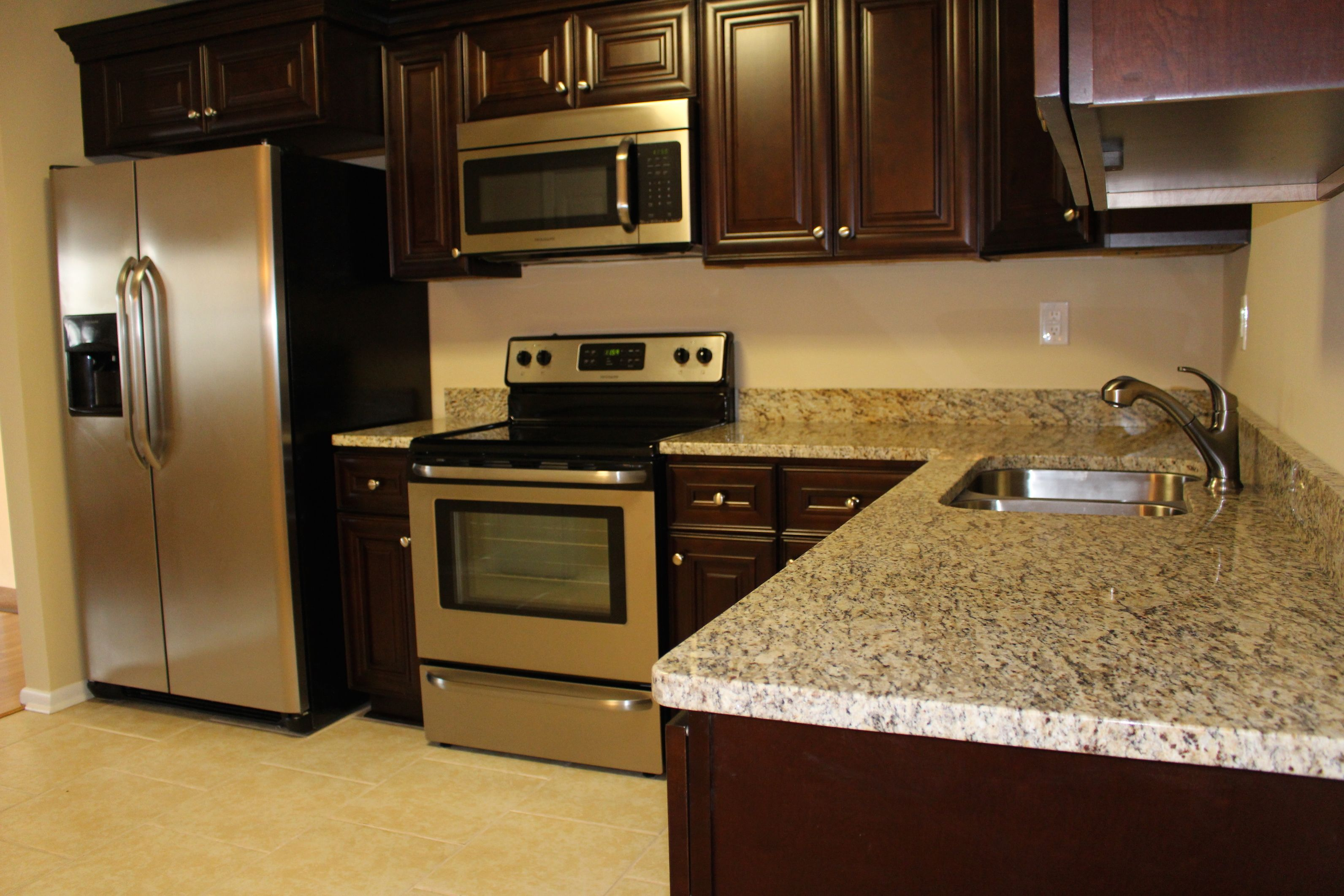 Dark cabinets and light granite countertops add a splash of bling with stainless steel appliances and you have ONE Rockstar Kitchen!
