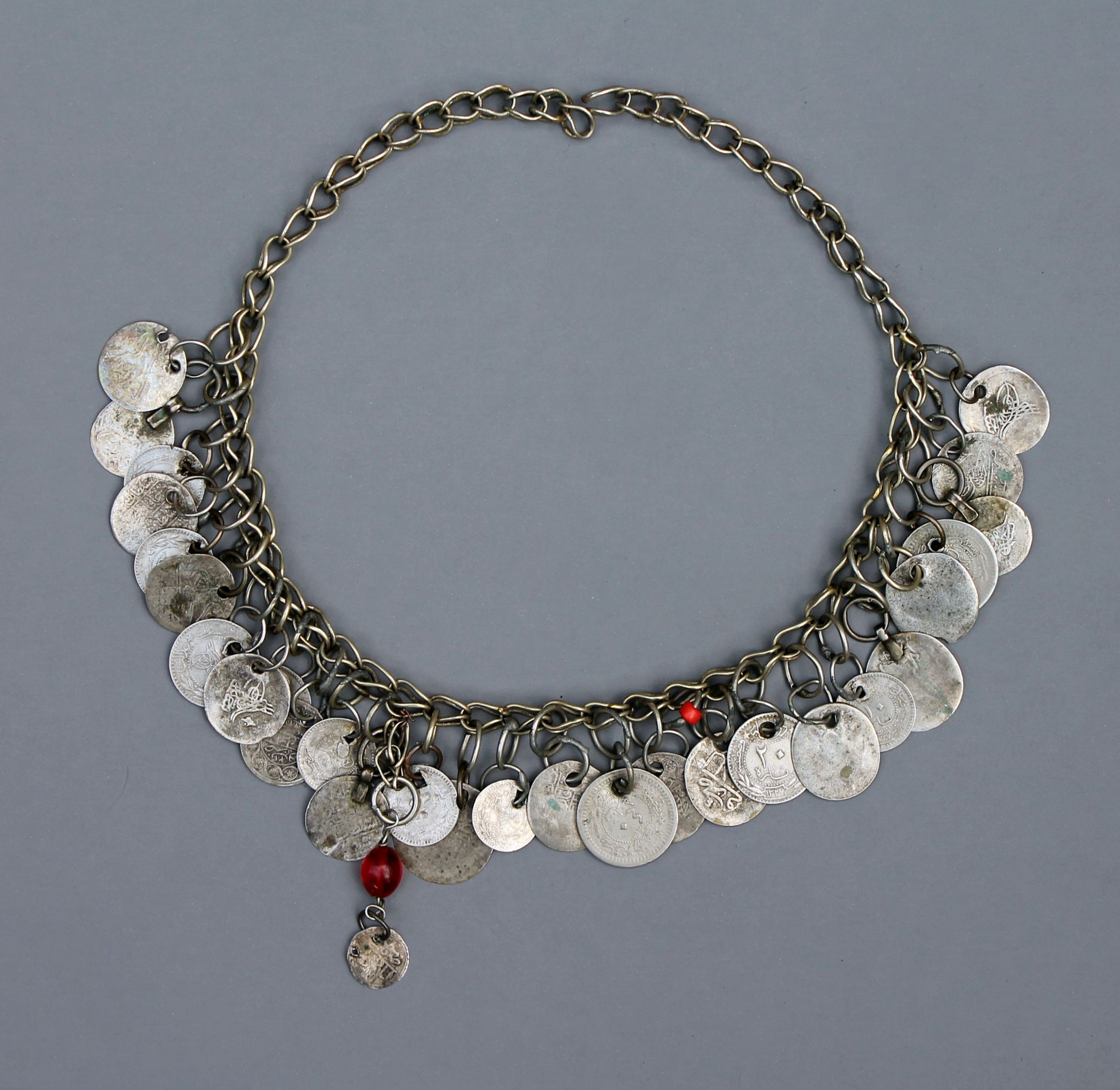 A silver necklace or head ornament with many old coins and a few ...