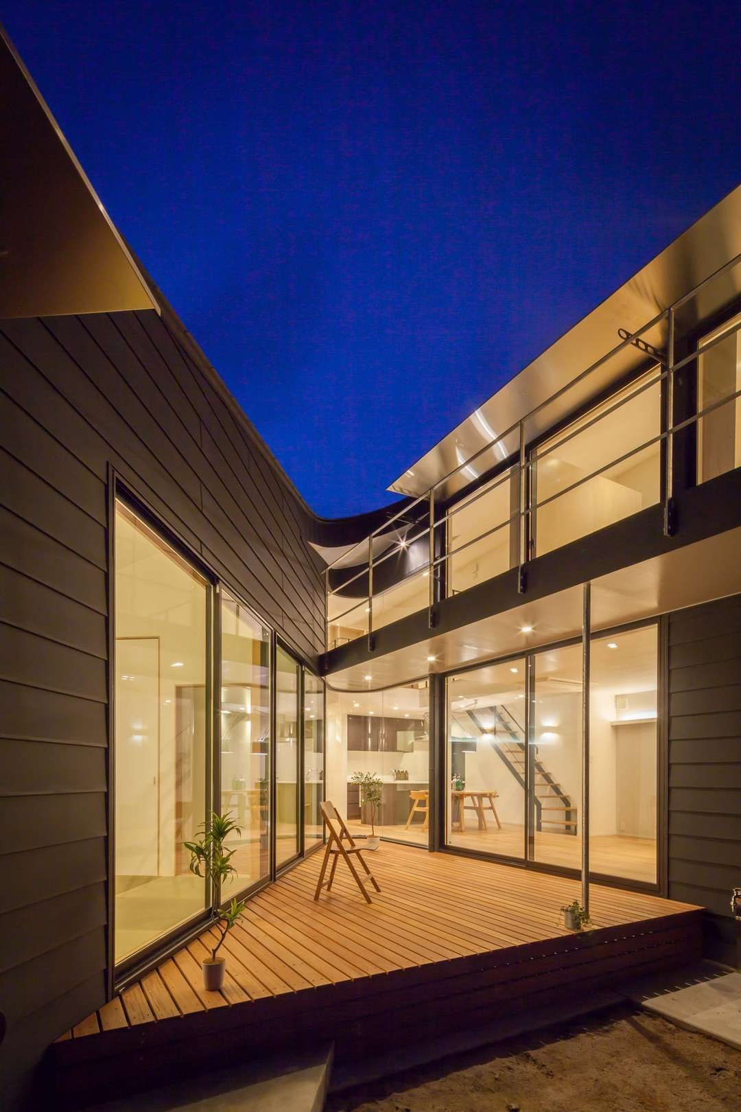 House at ureshino by tko m architects this boomerang shaped structure gradually doubles in height as it bends around a semi private courtyard
